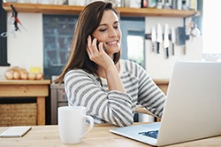 Smiling woman looking insurance on laptop and talking on phone