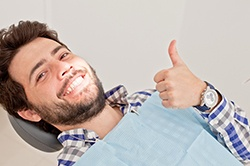 man giving thumbs-up in dentist's chair