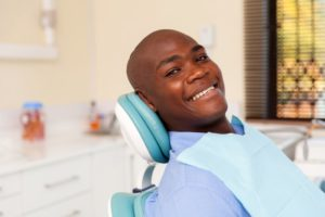person smiling and sitting in dentist's chair