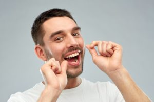 Man with healthy teeth flossing.