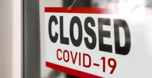 "Sign hanging on door reads ""CLOSED COVID-19"""
